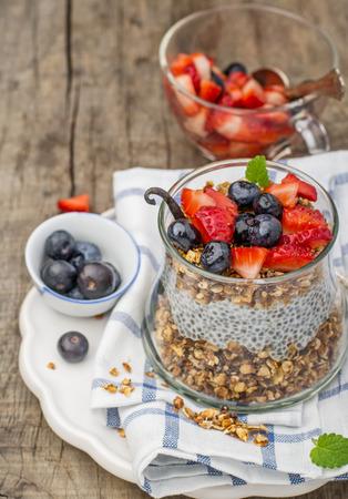 Chia Samen Pudding mit Heidelbeeren, strawberriesvanilla und Minze auf einem hölzernen Hintergrund. Selektiver Fokus. Das Konzept der gesunde Ernährung Standard-Bild - 37912029