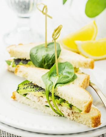 lemon slices: Panino appetitoso con pollo, spinaci, avocado e semi di papavero su un piatto di porcellana bianca su una tovaglia di pizzo bianco vintage con fette di limone. Messa a fuoco selettiva Archivio Fotografico
