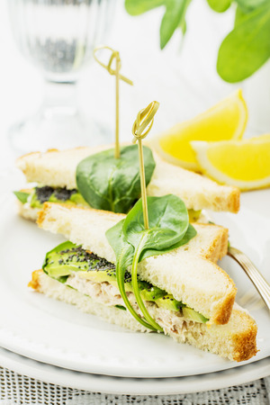 lemon slices: Appetizing sandwich with chicken, spinach, avocado and poppy seeds on a white china plate on a white lace tablecloth vintage with lemon slices. selective Focus Stock Photo