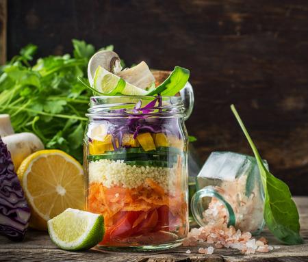 ensalada: Brillantes capas ensalada arco iris de tomates, zanahorias, cuscús, pimiento amarillo, lombarda, rúcula y setas con la mantequilla y la sal del mar en una rosa de verduras y hierbas de fondo. Tendencias de la alimentación saludable. Enfoque selectivo. Foto de archivo