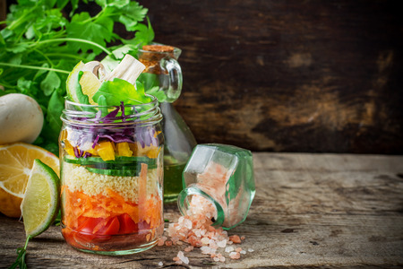 Bright rainbow salad layers of tomatoes, carrots, couscous, yellow pepper, red cabbage, arugula and mushrooms with butter and sea salt on a pink background vegetables and herbs. Trends in healthy eating. Selective focus. Stock Photo