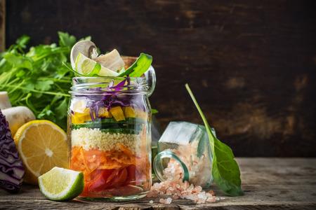 Brillantes capas ensalada arco iris de tomates, zanahorias, cuscús, pimiento amarillo, lombarda, rúcula y setas con la mantequilla y la sal del mar en una rosa de verduras y hierbas de fondo. Tendencias de la alimentación saludable. Enfoque selectivo.