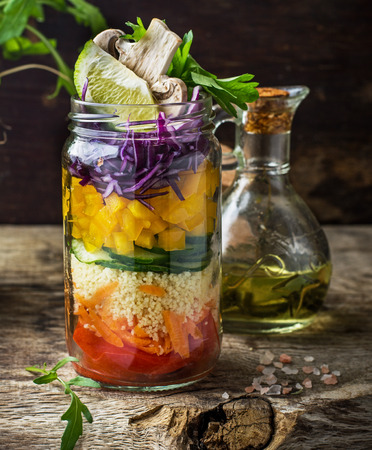 jar: Salad with assorted vegetables and herbs on a wooden background and the background of greens and vegetables. The concept of healthy snacks on the road and on the job. Trends in food. selective Focus
