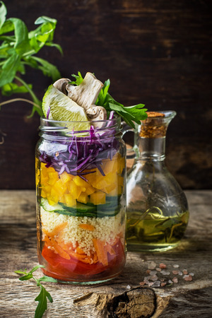 Rainbow salad in a jar of layers of different vegetables, mushrooms and herbs on dark wooden background surrounded by fresh vegetables and mushrooms. Concept of healthy food. selective Focus