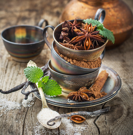 Cocoa powder, anise, vanilla sugar, vanilla pods in vintage silver cup on a wooden background with vintage coffee pot in the background. selective Focus photo