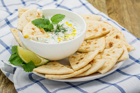 Refreshing sauce based on Greek yogurt, cucumber, dill, garlic, salt and butter as a sauce for vegetables, meat, bread. Served in a white plate with slices of pita bread, a slice of lime and fresh dill on a wooden background. selective Focus Standard-Bild