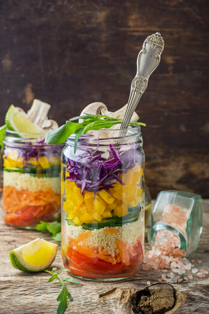 Bright rainbow salad  of tomatoes, carrots, pepper, red cabbage, arugula and mushrooms with butter and sea salt on a pink background vegetables and herbs. Trends in healthy eating. Selective focus. 版權商用圖片 - 38445841
