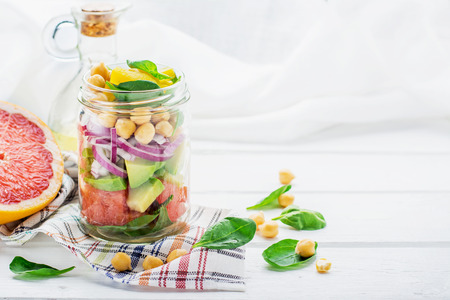 food dressing: Fresh spring salad of grapefruit, avocado, sweet onion, spinach and chickpeas in a glass jar for a snack with you on a picnic in the country, to work. The concept of healthy proper nutrition for the whole family. selective Focus