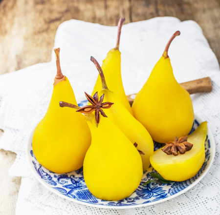 confiserie: Sweet fragrant pears poached with saffron and spices. Served on a wooden background. Selective soft focus