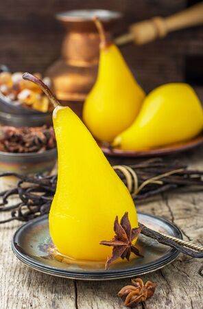 dekorated: Sweet fragrant pears poached with saffron and spices. Served on a wooden background. Selective soft focus