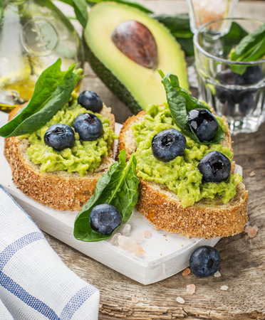 Avocado sandwich and blueberry on the wooden background with sea salt and spinach. selective Focus