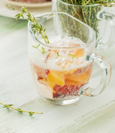 sprigs: Cool fruity cocktails, soda water served on a wooden tray decorated with flowers, raspberries, sliced nectarine and sprigs of thyme. Selective focus
