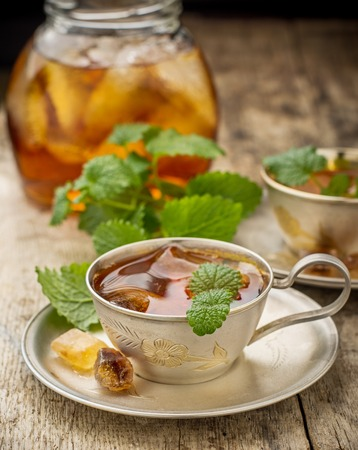 cool mint: Cool summer tea with mint and ice cubes in a silver cup on a wooden background. selective Focus