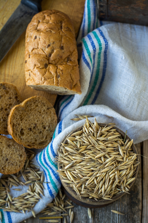 ear checked: Oat and bread on the wooden background with blue linen napkin. Selective focus. View from above. Stock Photo
