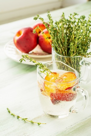water thyme: Sweet fizzy drink with peach slices and thyme on a light background. selective Focus Stock Photo