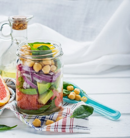 Fresh spring salad of grapefruit, avocado, sweet onion, spinach and chickpeas in a glass jar for a snack with you. The concept of healthy proper nutrition for the whole family. selective Focus