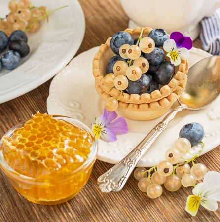 carte: Light fresh crunchy pastry tartlet of fresh blueberries and white currants on a la carte dishes with honey comb in the background Bunch of viola on a wooden background. selective Focus