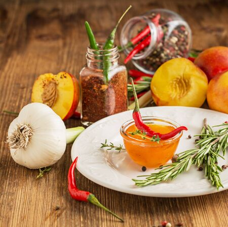 hot sauce: Home sweet fresh hot sauce made with fresh peaches and hot pepper to the meat and poultry in portion bowl with herbs, pepper and garlic on a white ceramic plate on a wooden background. yborochny focus. concept of healthy homemade food