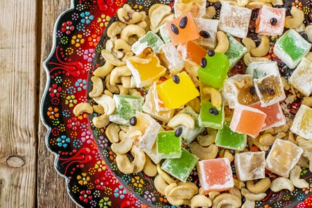 delight: Turkish delight with colorful chocolate seeds and cashew nuts at the national dish with hand-painted on a wooden background. selective Focus