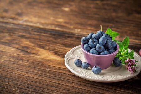 sweet table: Lilac bowl with blueberries on a white ceramic saucer on dark wooden background. selective Focus