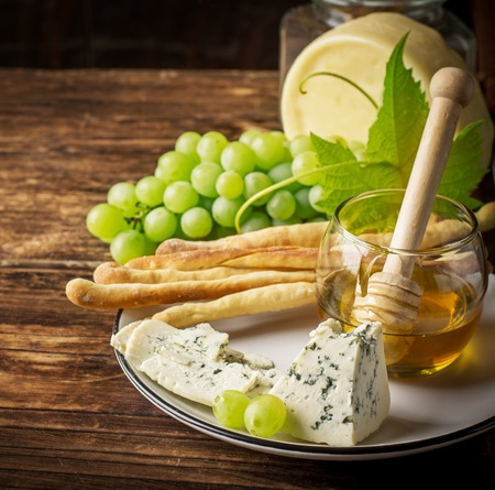 grissini: Composition with grissini, ripe grapes, assorted cheeses with fresh honeycombs with honey spoon on dark wooden background. selective Focus