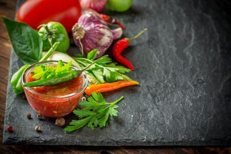 black stone: Spicy sweet tomato sauce with onion, garlic, pepper and herbs in a glass bowl surrounded by vegetables, spices and herbs on a black stone plaque. selective Focus Stock Photo