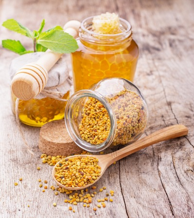 Bee pollen on a wooden background surrounded by jars of fresh honey and honeycombs. selective Focus