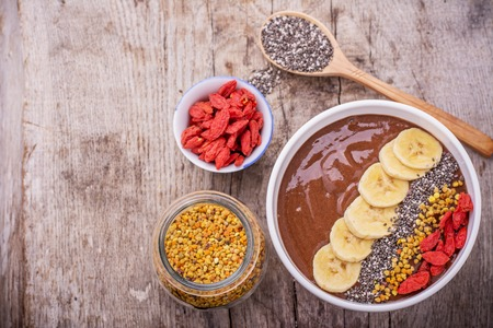 A bowl of breakfast with chocolate banana smoothies garnished with bee pollen, chia seeds, goji berries and banana slices on a wooden background. The concept of proper nutrition. Top view, Selective Focus Banco de Imagens