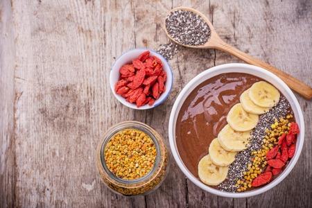 smoothies: Un tazón de desayuno con batidos de plátano de chocolate adornado con polen de abeja, las semillas de chía, las bayas de goji y rodajas de plátano en un fondo de madera. El concepto de una nutrición adecuada. Vista superior, Foco