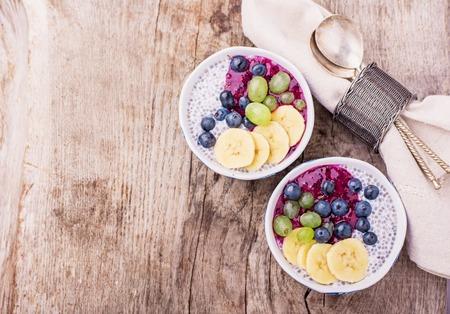 Chia Pudding zum Frühstück in Schalen in zwei Portionen auf einem hölzernen Hintergrund mit einer Serviette und Löffel, garniert mit Beeren-Smoothies, Trauben, Blütenblätter von Mandel-und Heidelbeere. Draufsicht. Tiefenschärfe Standard-Bild - 44372943