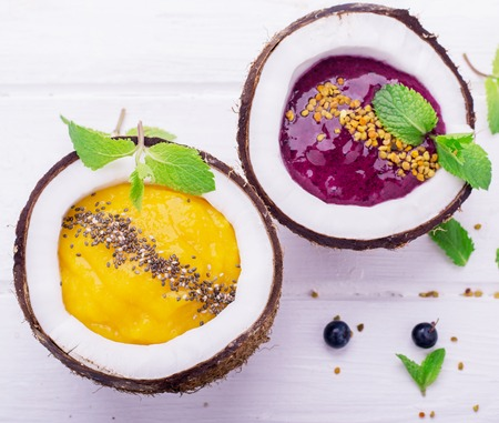 A healthy breakfast smoothie mango and berries garnished with chia seeds and bee pollen in two coconuts on a light wooden background. Concept of healthy food. Top view. selective Focus 版權商用圖片 - 44382648