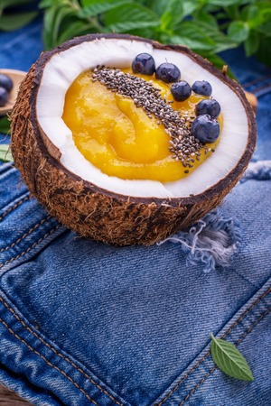 energized: Breakfast mango and berry smoothies garnished with chia seeds and bee pollen in coconut on jeans background. Concept of healthy food. selective Focus