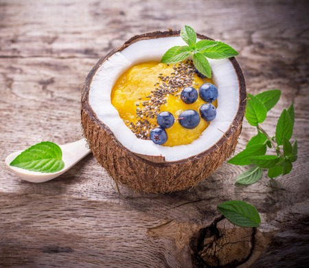 Mango smoothies for breakfast with a garnish of chia seeds in the shell of a coconut on a wooden background with berries, blueberries and mint leaves. selective Focus Stock Photo