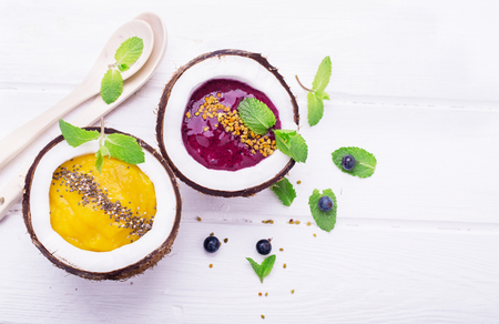 A healthy breakfast smoothie mango and berries garnished with chia seeds and bee pollen in two coconuts on a light wooden background. Concept of healthy food. Top view. selective Focus