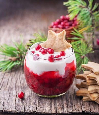 Dessert with cranberry sauce and sour cream decorated gingerbread cookies in the shape of stars and fresh berries cranberries in glasses on dark wooden background. selective Focus 版權商用圖片