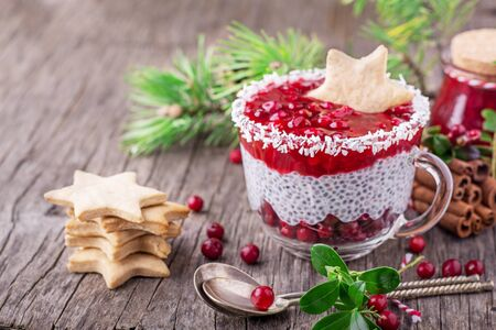 seed: Festive breakfast of cranberry sauce and pudding of chia seeds is decorated with homemade ginger biscuits in the shape of a star in a glass bowl on dark wooden background. selective Focus