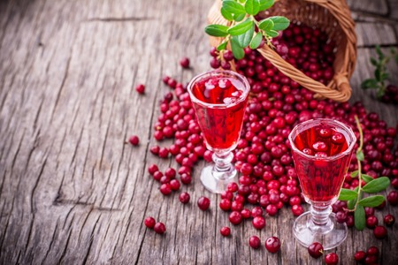 Sweet cranberry liqueur in two glasses on the background of ripe berries on a dark wooden background. selective Focus 免版税图像