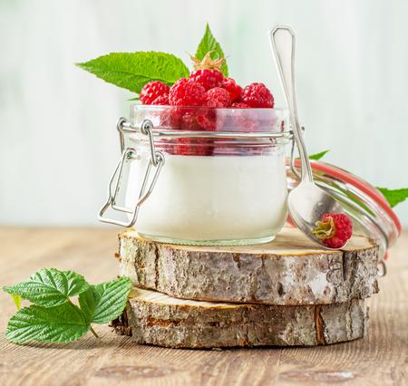 yogur: Tarro de yogur casero fresco con frambuesas frescas maduras para el desayuno en un fondo de madera. El concepto de alimentos naturales saludables. Enfoque selectivo