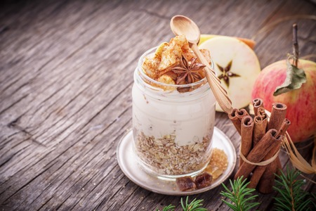 eating yogurt: Overnight Oatmeal with yogurt, slices of fresh apples in the batch of ground cinnamon in a glass jar on a wooden background with apples, cinnamon sticks and honey. The concept of healthy natural foods. selective Focus Stock Photo
