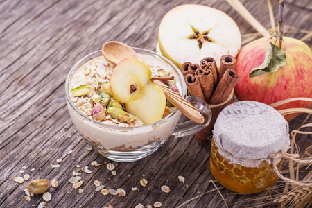 Overnight Oatmeal with yogurt, ground cinnamon and caramel flavored slice of apple in a glass bowl on a wooden background with honey, pistachios, cinnamon sticks and apple. The concept of healthy organic food. selective Focus Stock Photo
