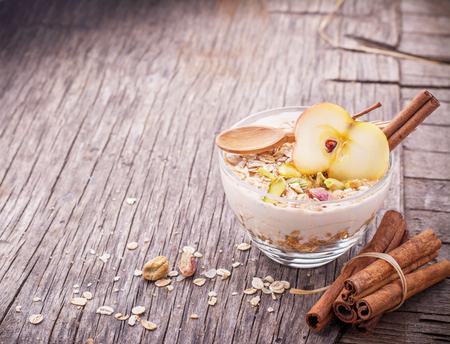 overnight: Overnight Oatmeal with yogurt, ground cinnamon and slice of apple in a glass bowl on a wooden background with honey, pistachios, cinnamon and apple. The concept of healthy food. selective Focus
