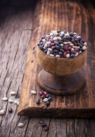 turtle bean: Colored assorted beans in old wooden bowl on dark wooden background. selective Focus Stock Photo