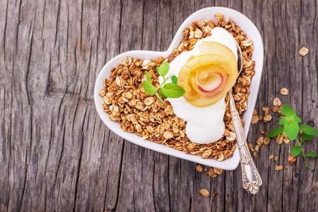 alimentacion sana: Granola con yogur y manzana de caramelo rebanadas dobladas en forma de una rosa yema en un plato blanco en la forma de un corazón en un fondo de madera. Vista superior. Gorizonal. Enfoque selectivo