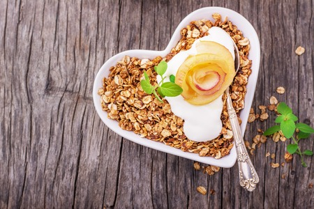 healthy grains: Granola with yogurt and caramel apple slices folded in the shape of a rose bud in a white plate in the shape of a heart on a wooden background. Top view. Gorizonal. selective Focus