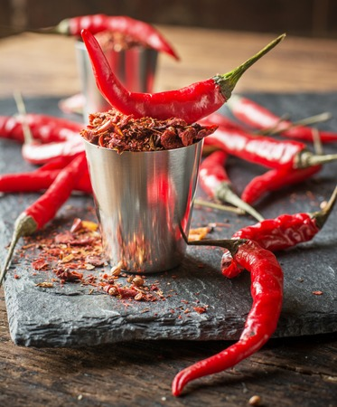 Hot pepper in a metal cup on a dark background with fresh bright red chili pepper pods. selective Focus Standard-Bild