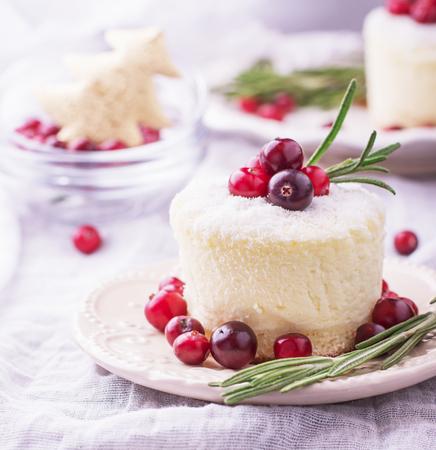cocotier: petites portions cheesecakes avec des canneberges mûres et de romarin parsemé de flocons de noix de coco sur un textile fond clair. Mise au point sélective