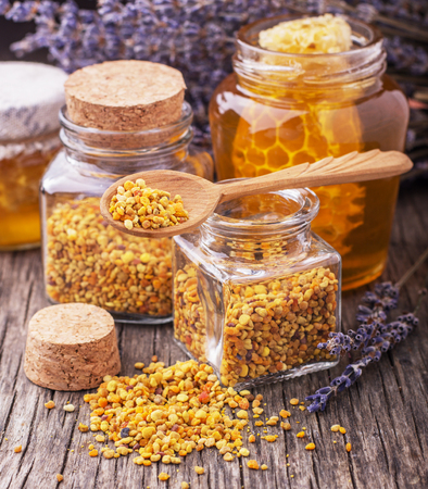 Golden bee pollen in small glass jars with honey comb on the texture wooden background with the wooden spoon. Concept of healthy food. selective Focus 版權商用圖片