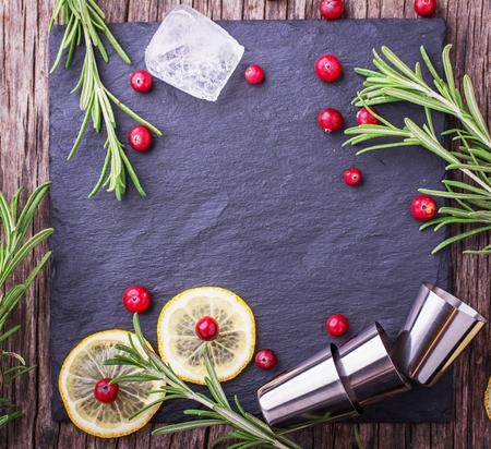 cocteles: Ingredientes para coctel de arándanos con limón y romero en una vista superior de piedra negro de la tabla con los cubos de hielo y vasos de cóctel de metal. Enfoque selectivo