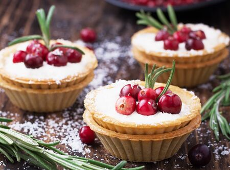 pastry: Tartlets of pastry with cream and fresh berries ripe cranberries and rosemary leaves sprinkled with coconut on the texture wooden background. selective Focus Stock Photo