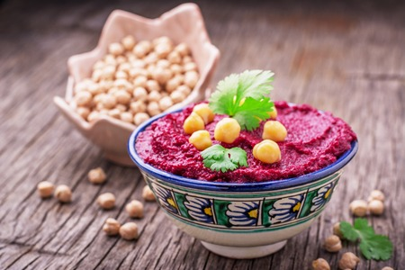 Beetroot hummus with chickpeas and cilantro sprigs in a blue painted bowl on dark wooden background. selective Focus